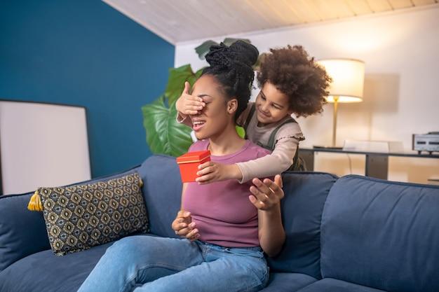 Surpresa de sorte. filha afro-americana com presente, fechando os olhos para a jovem mãe alegre em pé atrás do sofá na sala