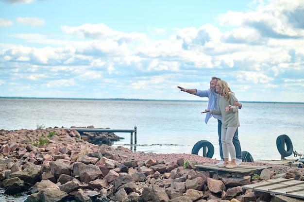 Surpresa, deleite. homem maduro e alegre surpreso com a mão estendida e mulher olhando com interesse em pé perto do mar