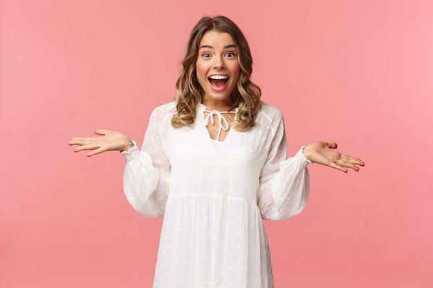 Surpresa e feliz jovem loira espalhou as mãos sorrindo para o lado, em pé parede rosa sorte e otimista.
