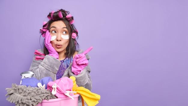 Surpresa e maravilhada jovem asiática indica, na área de cópia, poses perto da lavanderia, ocupada fazendo tarefas domésticas isoladas sobre a parede roxa