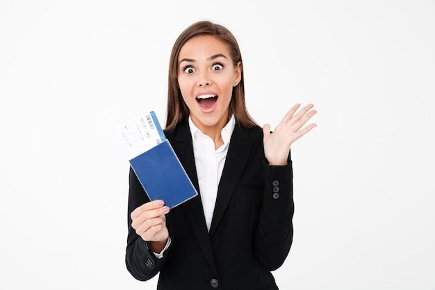 Surpresa empresária bonita animada segurando bilhetes e passaporte
