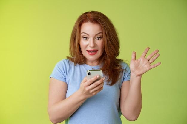 Surpresa, entusiasmada, feliz, ruiva, madura, mulher, de meia idade, receber, excelente, mensagem, ler, perfeitas, notícias, mídia social, segurar, smartphone, olhar surpreso