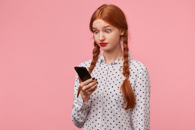 Surpresa espantada garota espantada reagir a uma mensagem de sua amiga, segurando um telefone nas mãos e olhando para ele olhos redondos grandes e abertos meia volta isolados em um rosa