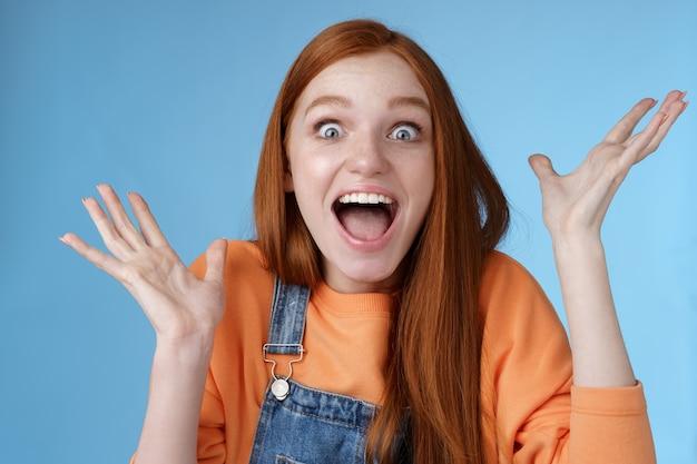 Surpresa espantada sensível oprimida jovem feliz ruiva recebe incrível prêmio fantástico olhos arregalados espantado levantando as mãos triunfando ganhar loteria comemorando com alegria.