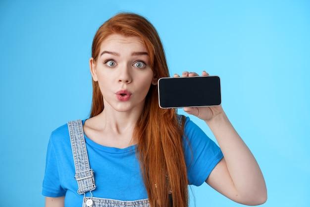 Surpresa, fascinada e animada, mulher ruiva dos anos 20 mostra a tela do smartphone horizontalmente, lábios dobrados assobiando divertidos imaginando, verifique o aplicativo de telefone legal, fique com um fundo azul curioso