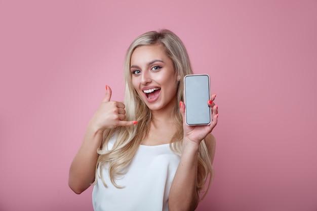 Surpresa feliz mulher loira mostrando o telefone na parede rosa