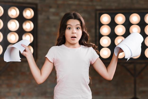 Surpresa garota em frente a luz de palco segurando scripts