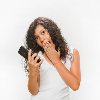 Surpresa garota segurando o telefone móvel