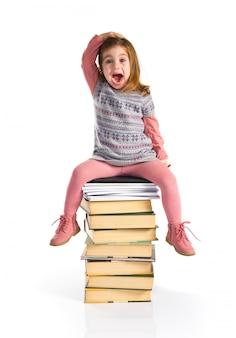 Surpresa garotinha sentado nos livros. de volta à escola