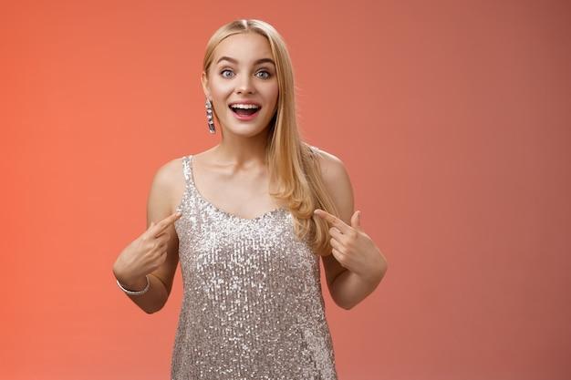 Surpresa imaginou feliz loira encantadora mulher alegre em vestido prata cintilante apontando para si mesma divertida emocionada escolhida ser escolhida participar de evento incrível, em pé alegre fundo vermelho.