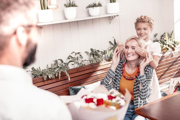 Surpresa incrível. mulher simpática e simpática sorrindo enquanto recebe um buquê de flores