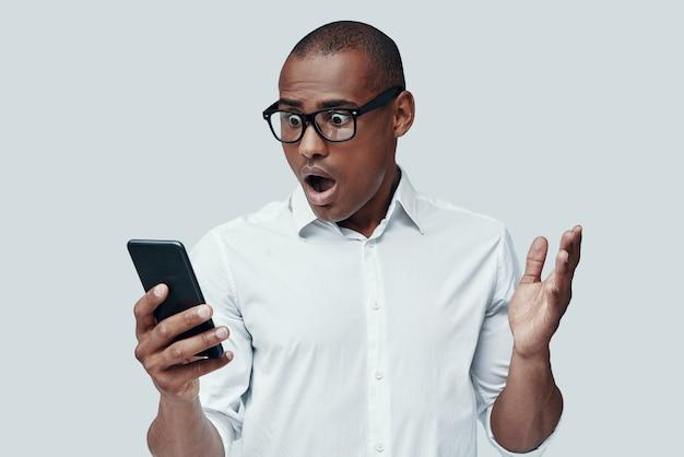 Surpresa. jovem africano chocado usando um telefone inteligente em pé contra um fundo cinza