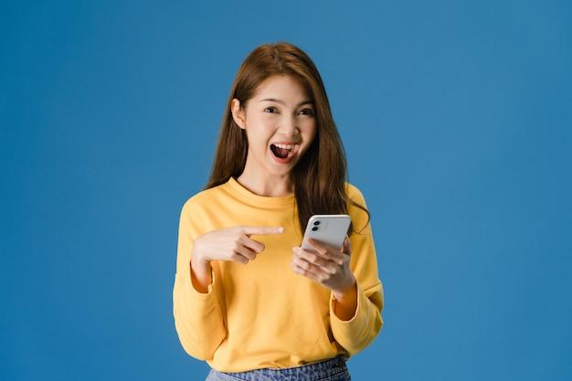 Surpresa jovem asiática usando telefone celular com expressão positiva, amplamente sorri, vestida com roupas casuais e olhando para a câmera sobre fundo azul. mulher feliz adorável feliz alegra sucesso.