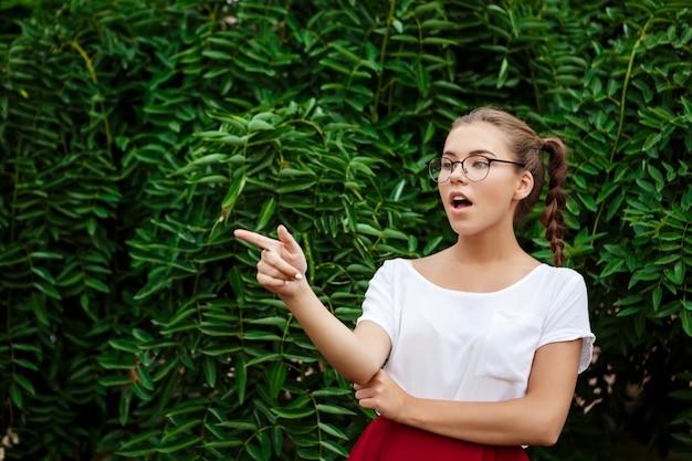 Surpresa jovem bela aluna de óculos, apontando o dedo para longe