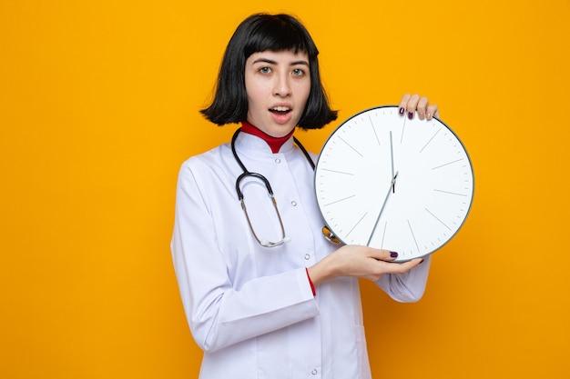 Surpresa, jovem, bonita, caucasiana, com uniforme de médico, com estetoscópio, segurando o relógio com as duas mãos