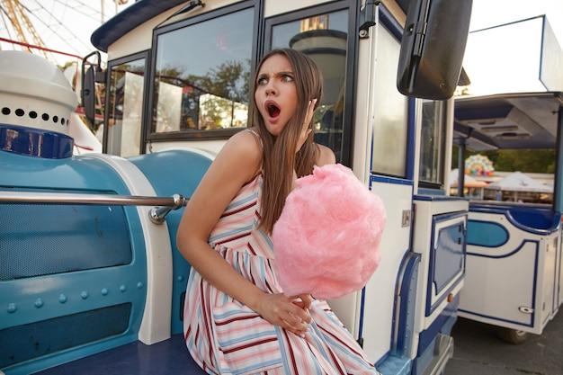 Surpresa, jovem e atraente senhora de cabelos compridos com algodão doce na mão, sentada no parque de diversões em um dia quente de verão, olhando de lado com a boca aberta e o rosto carrancudo