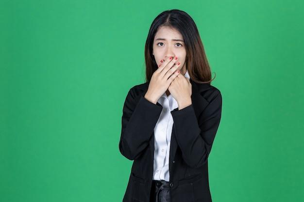 Surpresa jovem empresária asiática fecha a boca com as mãos