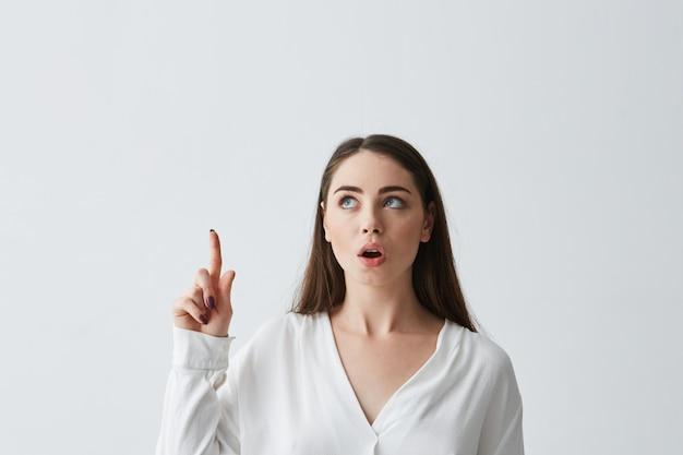 Surpresa jovem empresária linda com a boca aberta, apontando o dedo para cima.