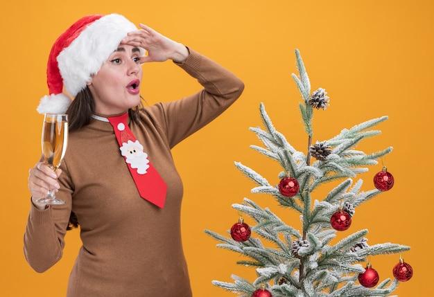 Surpresa jovem linda garota usando chapéu de natal com gravata em pé perto da árvore de natal segurando uma taça de champanhe, olhando para a distância com a mão isolada na parede laranja
