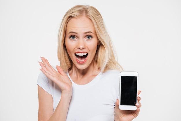 Surpresa jovem loira bonita com a boca aberta, mostrando a tela do smartphone em branco