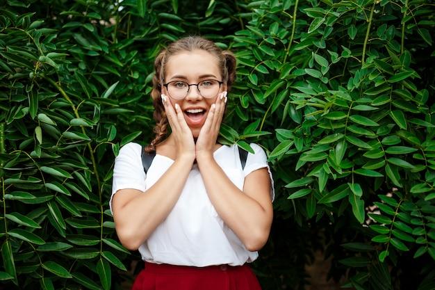 Surpresa linda aluna de óculos posando sobre folhas ao ar livre.