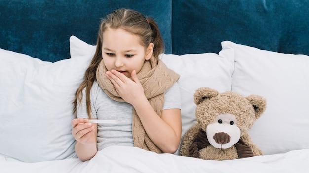Surpresa menina sentada perto do ursinho de pelúcia, sofrendo de febre olhando para termômetro