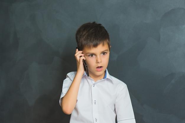 Surpresa menino na camisa branca falando ao telefone, o pequeno chefe.