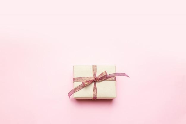 Surpresa mínima de caixa de presente de artesanato de natal com laço de fita dourada em rosa pastel.