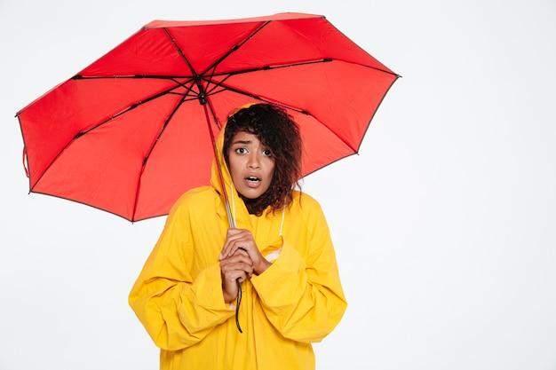 Surpresa mulher africana em capa de chuva posando com guarda-chuva