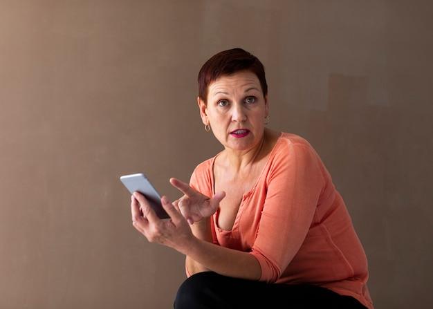 Surpresa mulher madura segurando smartphone
