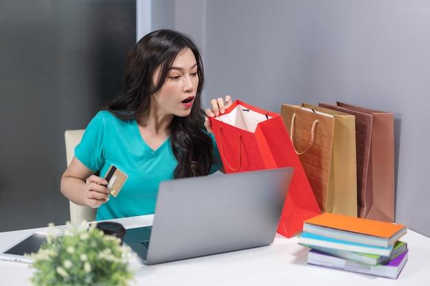 Surpresa mulher segurando o cartão de crédito e olhando para a sacola de compras na mesa