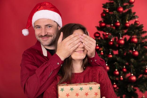 Surpresa romântica no natal, mulher bonita recebe presente do namorado, homem fecha os olhos da menina com as mãos.