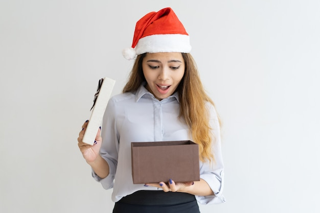 Surpresa senhora usando chapéu de papai noel e espiando na caixa de presente