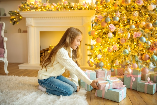Surpresas de natal. linda garota loira segurando presentes e parecendo interessada