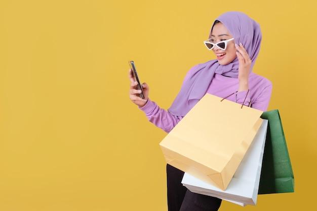 Surpresas lindas mulheres asiáticas viciadas em compras e um cartão de crédito segurando sacolas de compras e apontando algo