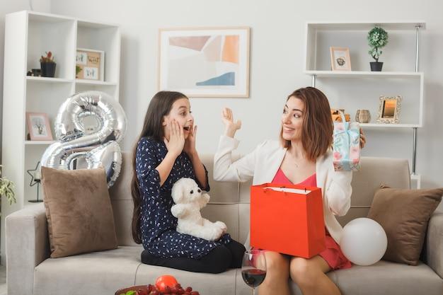 Surpresas, olhando uma para a outra, a garotinha e a mãe com um presente e um ursinho de pelúcia no feliz dia da mulher, sentadas no sofá na sala de estar
