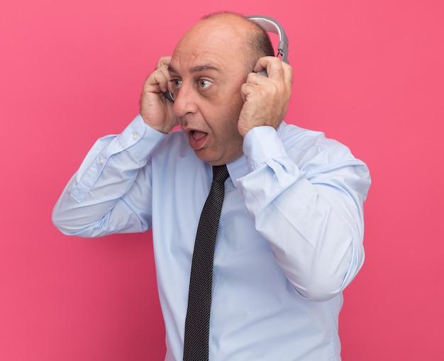 Surpreso ao olhar para o lado de um homem de meia-idade vestindo uma camiseta branca com gravata e fones de ouvido isolados na parede rosa