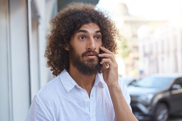 Surpreso, bonito, barbudo, com cabelo castanho encaracolado, andando pela rua com o celular na mão, testa franzida e sobrancelhas erguidas