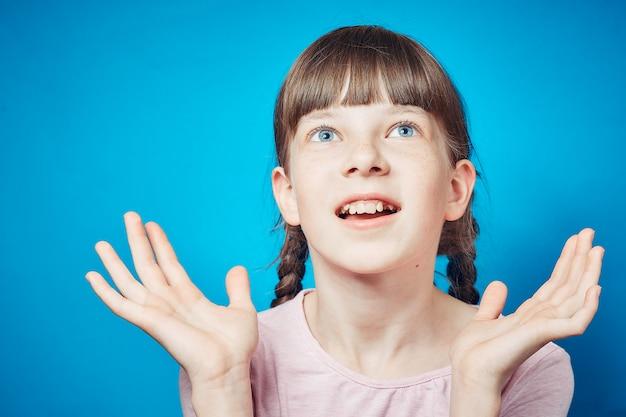 Surpreso chocado atônito espantado menina olhando para cima acima de sua cabeça