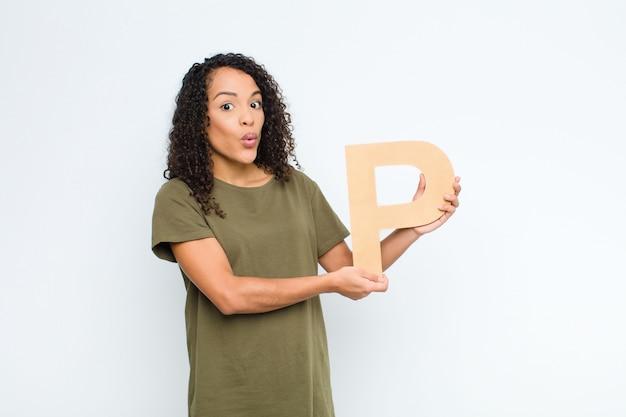 Surpreso, chocado, espantado, segurando a letra p do alfabeto para formar uma palavra ou frase.