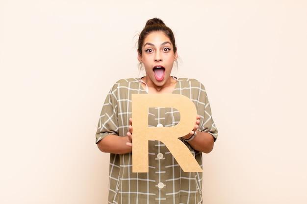 Surpreso, chocado, espantado, segurando a letra r do alfabeto para formar uma palavra ou frase.