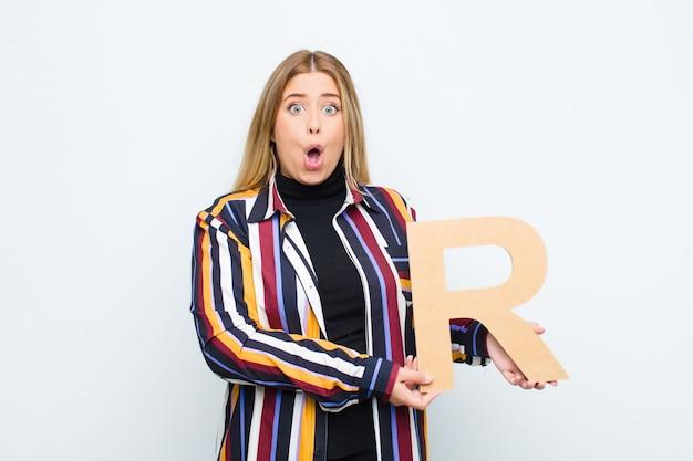 Surpreso, chocado, surpreso, segurando a letra r do alfabeto para formar uma palavra ou frase.