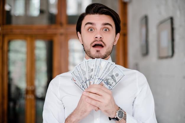 Surpreso e animado homem segurando dinheiro nas mãos