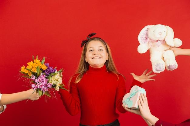 Surpreso e espantado. celebração do dia dos namorados. feliz, linda garota caucasiana isolada no fundo vermelho do estúdio. conceito de emoções humanas, expressão facial, amor, relações, férias românticas.