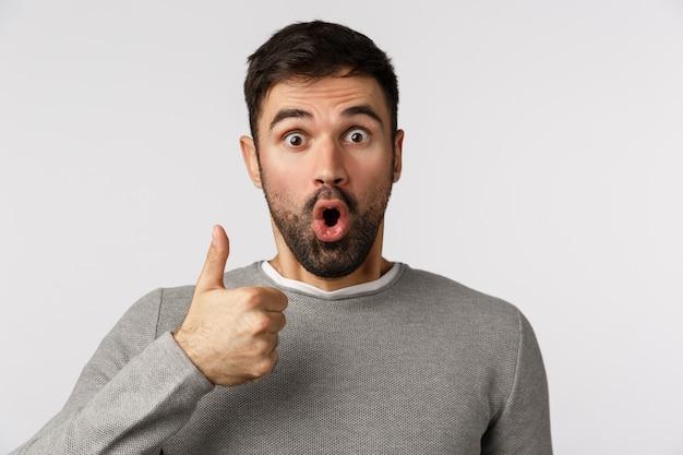 Surpreso e fascinado, espantado, barbudo, sem fala, de suéter cinza, reage a um maravilhoso evento divertido, mostra o polegar para cima em aprovação, aprovação ou gesto de aceitação, ofegando, diga uau