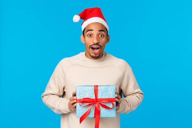 Surpreso entusiasmado e oprimido homem bonito afro-americano no chapéu de papai noel, roupa de natal, segurando o presente de ano novo de amigo e se divertindo, quer desembrulhar o presente, parede azul