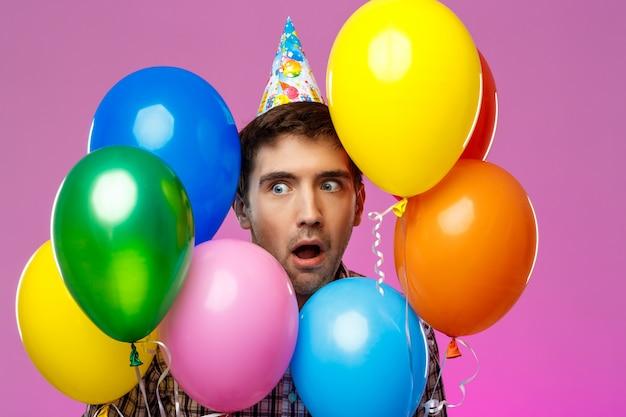 Surpreso homem comemorando aniversário, segurando balões coloridos sobre parede roxa.