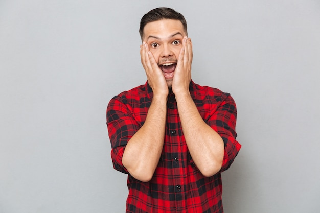 Surpreso homem feliz segurando suas bochechas
