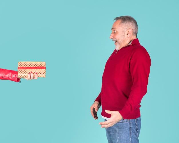 Surpreso homem maduro, olhando para a mão de uma mulher segurando embrulhado caixa de presente contra o fundo turquesa