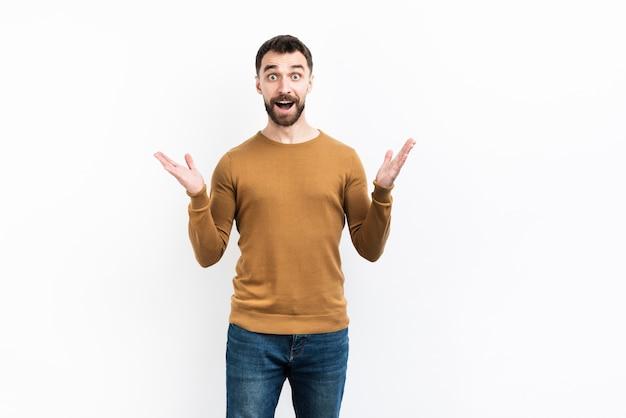 Surpreso homem posando com as mãos para cima